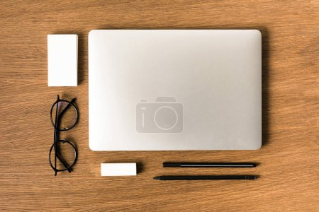 Photo for Flat lay with arranged laptop, eyeglasses, blank cards, pen and pencil on wooden tabletop - Royalty Free Image