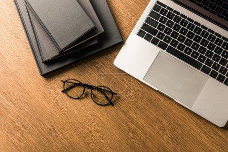 Photo pour Vue de dessus du pieu arrangé noirs ordinateurs portables, ordinateur portable, des lunettes sur la table en bois - image libre de droit