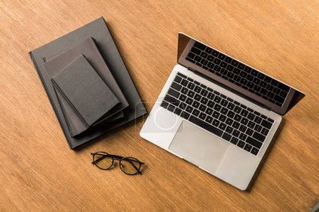 top view of arranged pile of black notebooks, laptop and eyeglasses on wooden tabletop