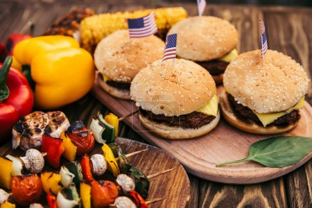 Hamburgers with flags and vegetables cooked outdoors on grill