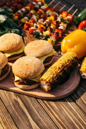 Burgers and corn cooked outdoors on grill