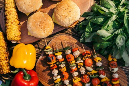 Vegetable on skewers and hamburgers grilled for outdoors barbecue