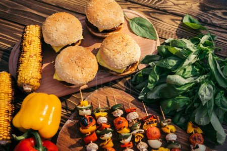Hot delicious burgers and vegetables cooked outdoors on grill
