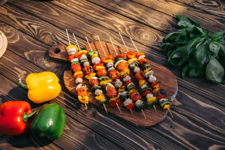 Wooden board with vegetables and mushrooms on skewers cooked outdoors on grill