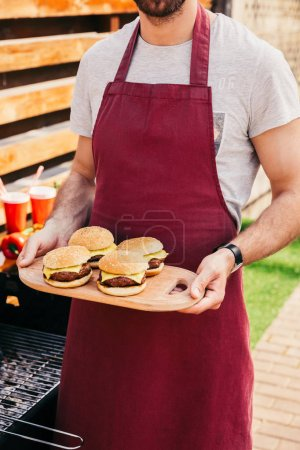 Close-up view of man holding board with burgers cooked outdoors on grill