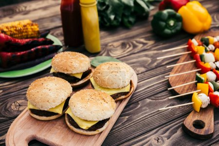 Photo for Hot delicious burgers and vegetables grilled for outdoors barbecue - Royalty Free Image