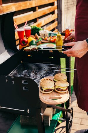 Man grilling meat for burgers on fire outdoors