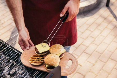 Man serving hamburgers cooked outdoors on grill
