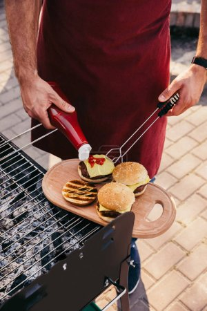 Chef adding ketchup to burgers grilled for outdoors barbecue