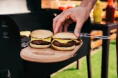 Man putting bun on meat of hamburgers grilled for outdoors barbecue