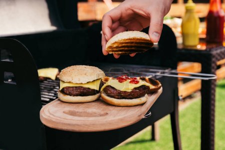 Chef serving hamburgers cooked outdoors on wooden board
