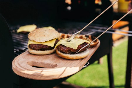 Serving tongs holding hot burgers grilled for outdoors barbecue