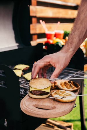 Man adjusting bun on meat of burgers cooked outdoors on grill