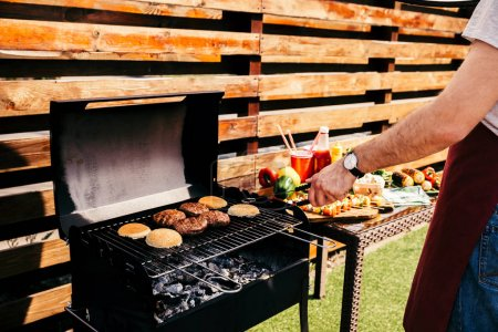 Man cooking grilled meat burgers for outdoors barbecue