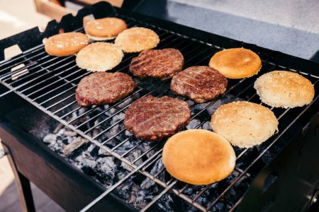 Buns and meat patties grilled for outdoors barbecue