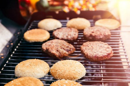Bread and meat cooked for burgers outdoors on grill