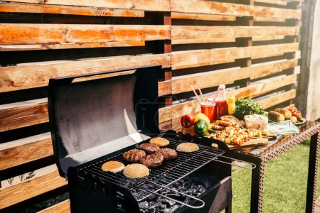 Seasonal vegetables and burgers cooked outdoors on grill