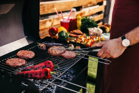 Photo for Chef cooking patties and vegetables grilled for outdoors barbecue - Royalty Free Image