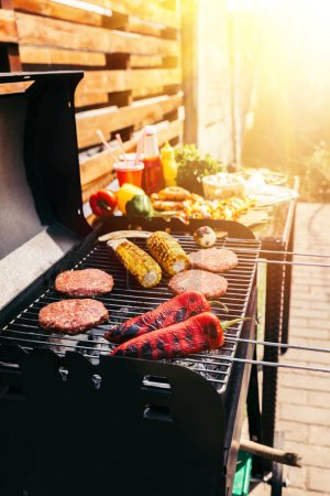 Burger patties and vegetables cooked outdoors on grill