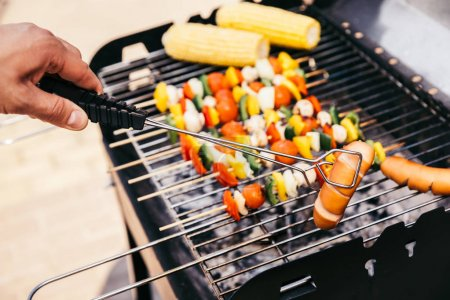 Chef checking vegetables and sausages cooked outdoors on grill