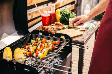 Man checking vegetables and sausages grilled for outdoors barbecue
