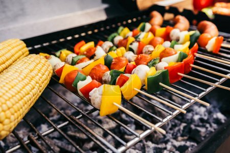 Sausages and vegetables on skewers grilled for outdoors barbecue