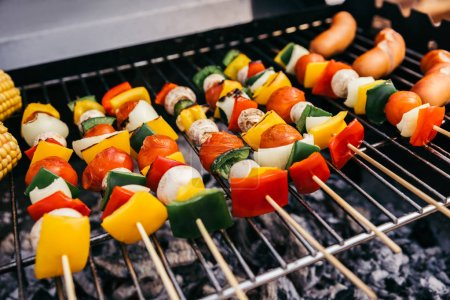 Summer vegetables with mushrooms on skewers and sausages grilled for outdoors barbecue