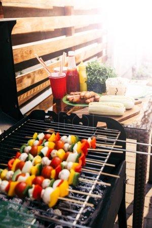 Seasonal vegetables and mushrooms on skewers cooked outdoors on grill