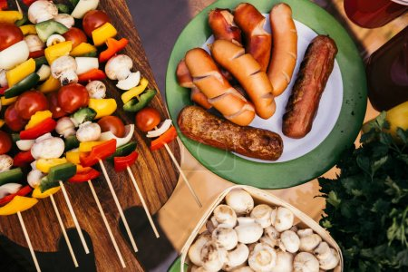 Table with sausages and vegetables with mushrooms grilled for outdoors barbecue