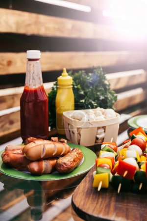 Hot sausages and vegetables with ketchup and mustard grilled for outdoors barbecue