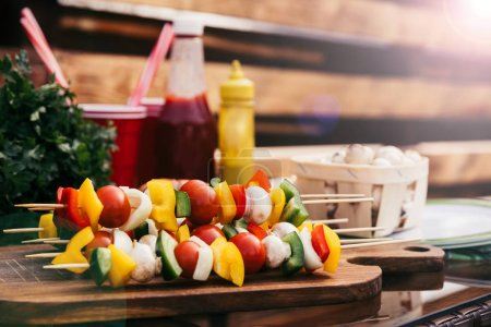 Vegetables on skewers with ketchup and mustard cooked outdoors