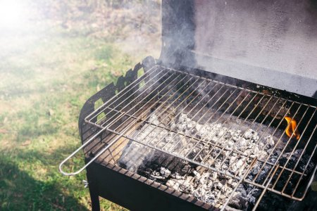 Grill with burning coals ready for barbecue outdoors