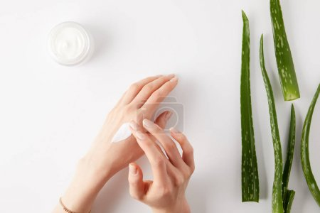 Photo for Cropped image of woman applying cream on hands, aloe vera leaves and cream in container on white surface - Royalty Free Image