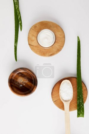 elevated view of organic cream in container and spoon with salt on wooden slices, aloe vera leaves and wooden bowl with aloe vera juice on white surface