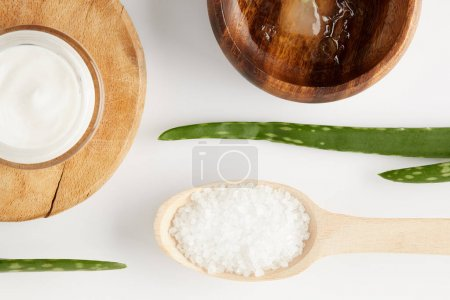 top view of organic cream in container, wooden bowl with aloe vera juice, spoon with salt and aloe vera leaves