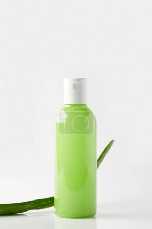 closeup view of organic shower gel in bottle and aloe vera leaf on white surface
