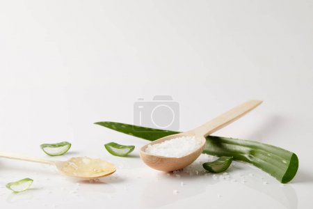 closeup view of two wooden spoons with aloe vera juice and salt, aloe vera leaf and slices on white surface