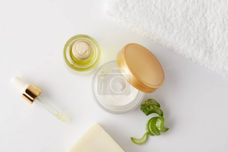 top view of organic cream, cosmetic oil and soap, pipette, towel and aloe vera slices on white surface