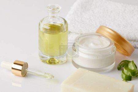 closeup shot of cosmetic oil, dropper, soap, towel, organic cream in container and aloe vera slices