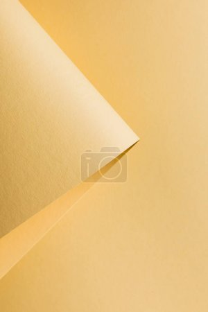 close-up view of rolled yellow paper sheet abstract background