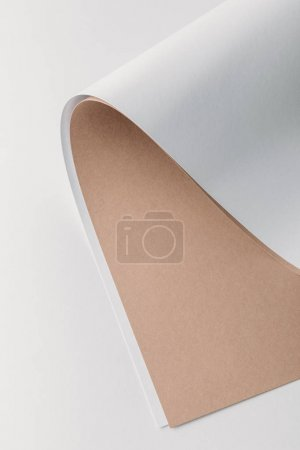 close-up view of white and brown rolled paper sheets on grey background