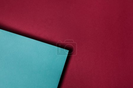 turquoise paper sheet on maroon background