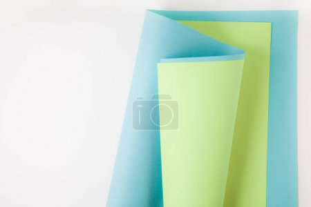blue and green paper sheets on grey background