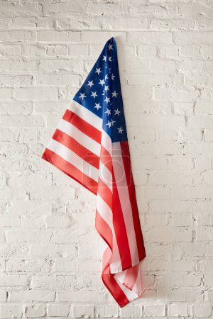 united states of america flag hanging on white brick wall
