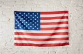 front view of united states of america flag on white brick wall
