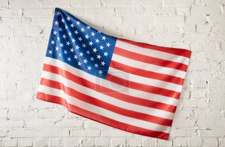 closeup shot of united states of america flag on white brick wall