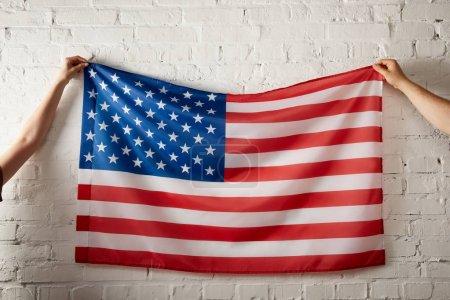 Photo pour Image recadrée de l'homme et de la femme tenant le drapeau américain contre un mur de briques - image libre de droit