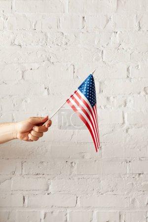 abgeschnittenes Bild eines Mannes, der eine amerikanische Fahnenstange gegen eine weiße Backsteinwand hält