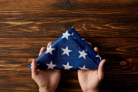Photo for Cropped shot of man holding folded united states flag on wooden background - Royalty Free Image