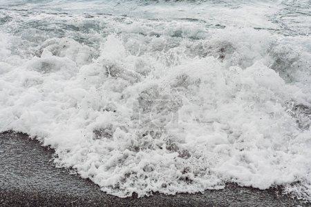 Photo for White sea foam on sandy beach - Royalty Free Image